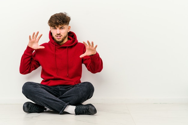 白で隔離された床に座っている若いモロッコ人男性は、猫を模倣した爪、攻撃的なジェスチャーを示しています。