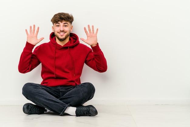 手で10番を示す白い壁に隔離された床に座っている若いモロッコ人男性。
