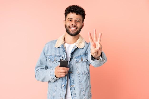 분홍색 배경에 행복하고 손가락으로 세 세에 고립 된 휴대 전화를 사용하는 젊은 모로코 남자
