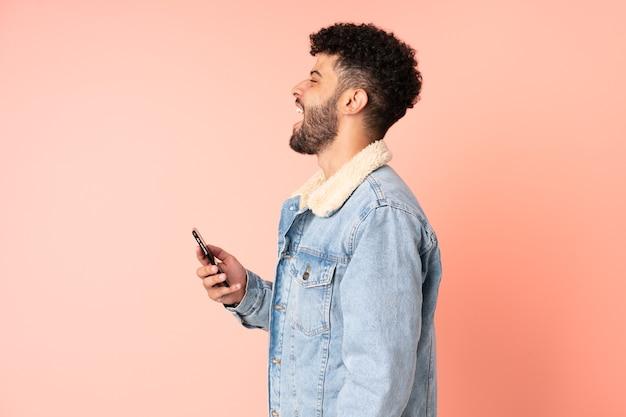 横向きの位置で笑ってピンクの背景に分離された携帯電話を使用して若いモロッコ人男性