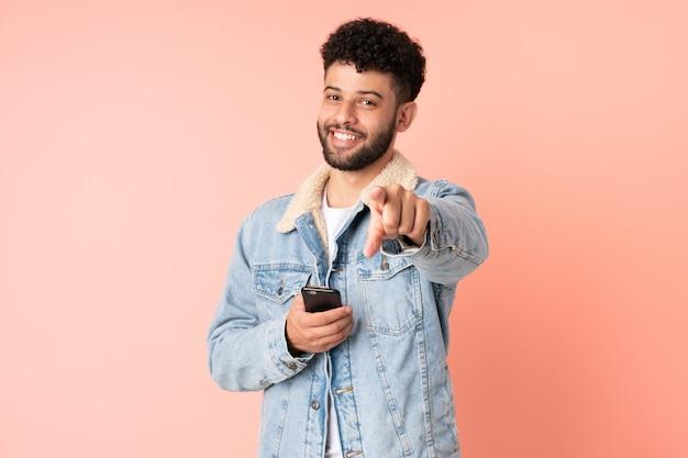 Молодой марокканский мужчина с помощью мобильного телефона изолирован на розовом фоне, указывая спереди с счастливым выражением лица