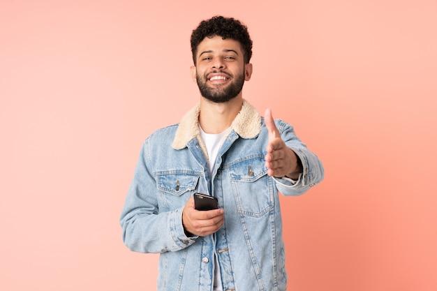 かなりの取引を閉じるために握手ピンクの背景に分離された携帯電話を使用して若いモロッコ人男性