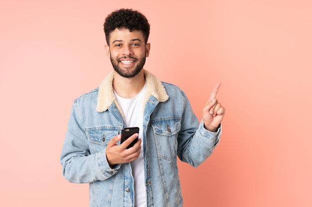 最高の兆候を示して指を持ち上げてピンクの背景に分離された携帯電話を使用して若いモロッコ人
