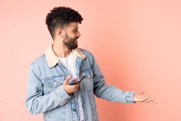 Молодой марокканский мужчина с помощью мобильного телефона изолирован на розовом фоне с удивленным выражением лица, глядя в сторону