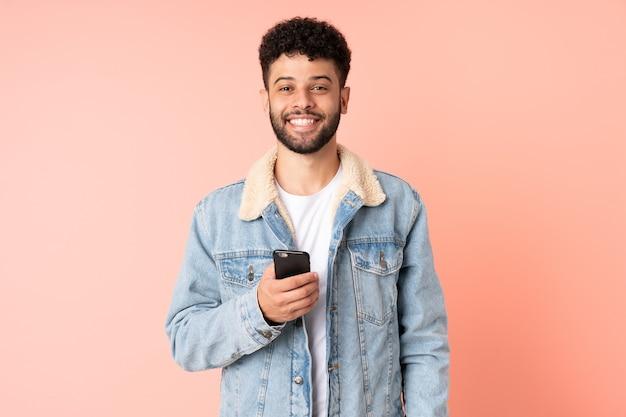 Молодой марокканский мужчина разговаривает по мобильному телефону на розовом фоне с удивленным выражением лица