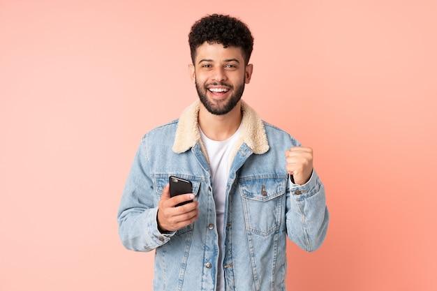 승자 위치에서 승리를 축하 분홍색 벽에 고립 된 휴대 전화를 사용하는 젊은 모로코 남자