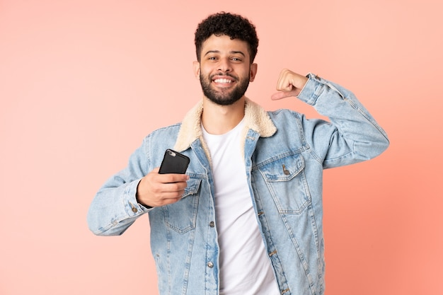 강한 제스처를 하 고 분홍색 벽에 고립 된 휴대 전화를 사용하는 젊은 모로코 남자
