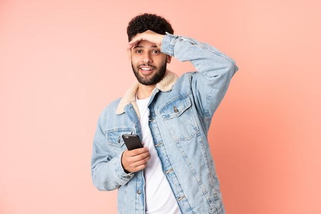 Молодой марокканский мужчина с помощью мобильного телефона, изолированного на розовой стене, делает неожиданный жест, глядя в сторону