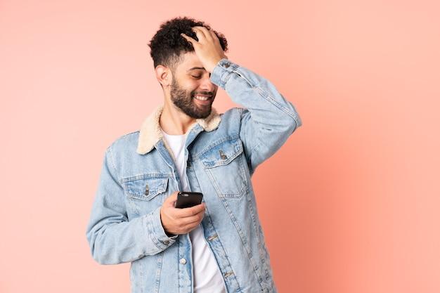 Молодой марокканец, использующий мобильный телефон на розовой стене, кое-что понял и намеревается найти решение