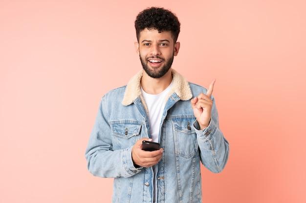 핑크 벽에 고립 된 휴대 전화를 사용하는 젊은 모로코 남자는 손가락을 들어 올리는 동안 솔루션을 실현하려는 의도