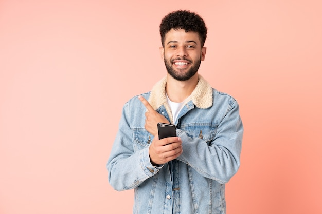 제품을 제시하기 위해 측면을 가리키는 분홍색 벽에 고립 된 휴대 전화를 사용하는 젊은 모로코 남자