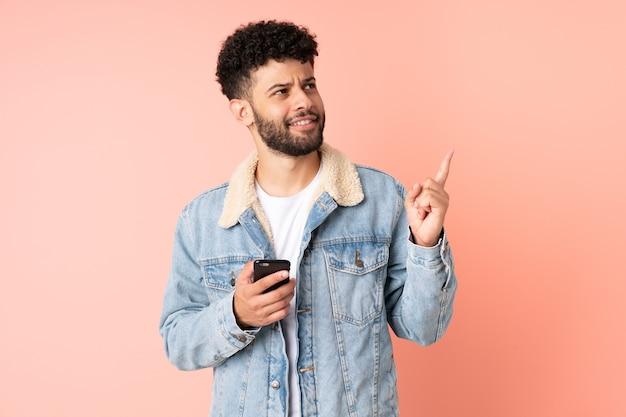 좋은 아이디어를 가리키는 분홍색 벽에 고립 된 휴대 전화를 사용하는 젊은 모로코 남자