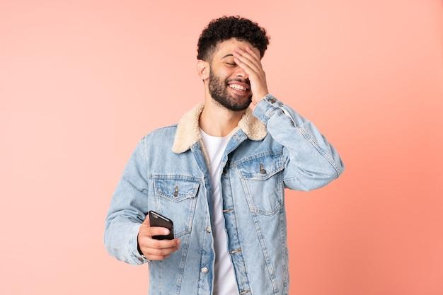 많이 웃고 분홍색 벽에 고립 된 휴대 전화를 사용하는 젊은 모로코 남자