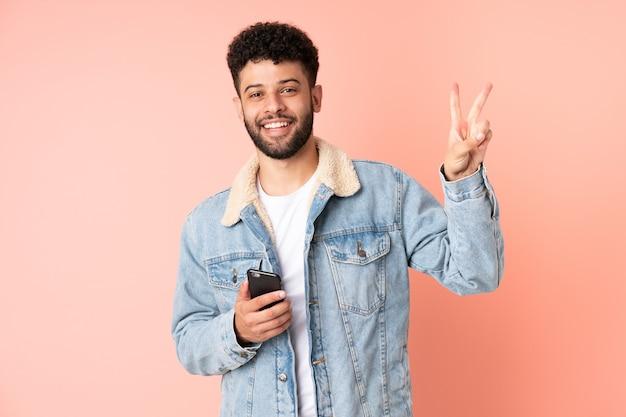 웃 고 승리 기호를 보여주는 분홍색 벽에 고립 된 휴대 전화를 사용하는 젊은 모로코 남자