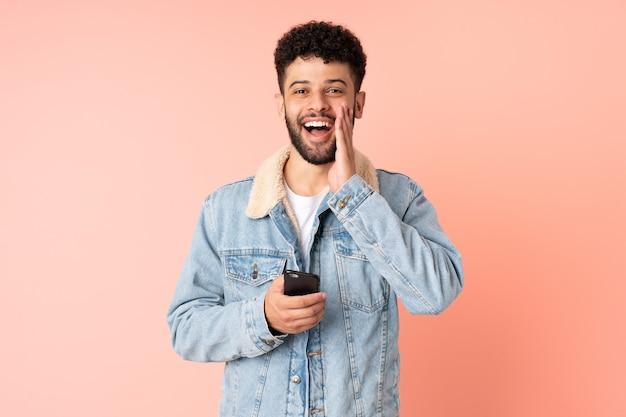 Молодой марокканский мужчина разговаривает по мобильному телефону на розовой стене с удивленным и шокированным выражением лица