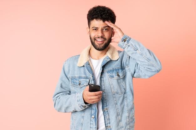 놀라운 표정으로 분홍색 벽에 고립 된 휴대 전화를 사용하는 젊은 모로코 남자