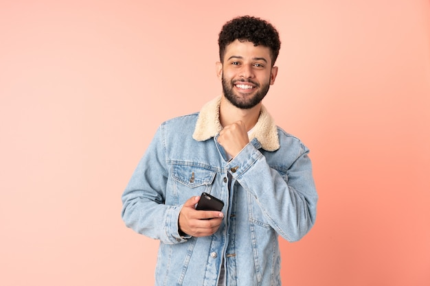 Young moroccan man using mobile phone isolated on pink celebrating a victory