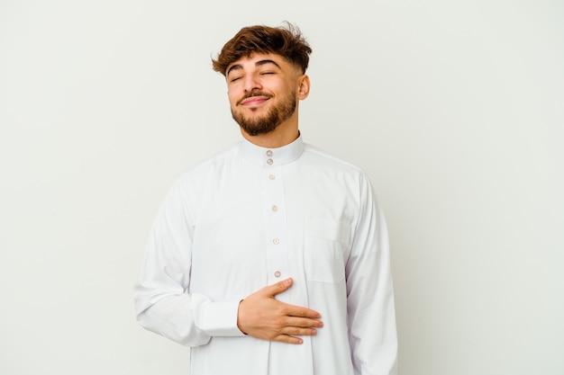 Молодой марокканский мужчина в типичной арабской одежде на белом трогает животик, нежно улыбается, ест и удовлетворяет концепции.