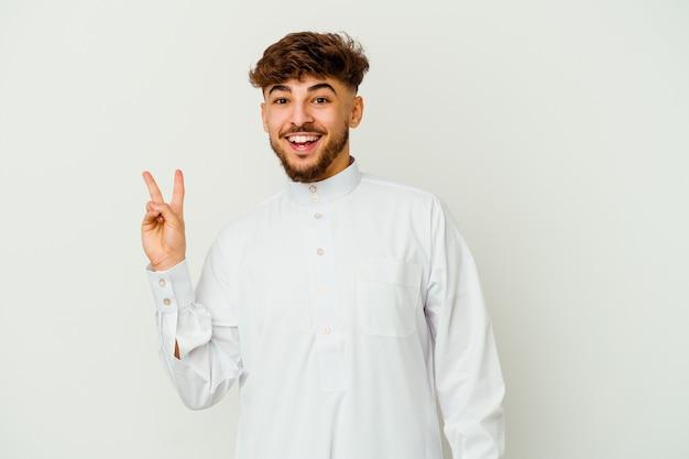 白い壁に隔離された典型的なアラブの服を着ている若いモロッコ人男性は、指で平和のシンボルを示して楽しくてのんきです。