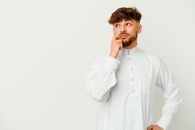 疑わしいと懐疑的な表現で横向きに見える白い壁に隔離された典型的なアラブの服を着ている若いモロッコ人男性。