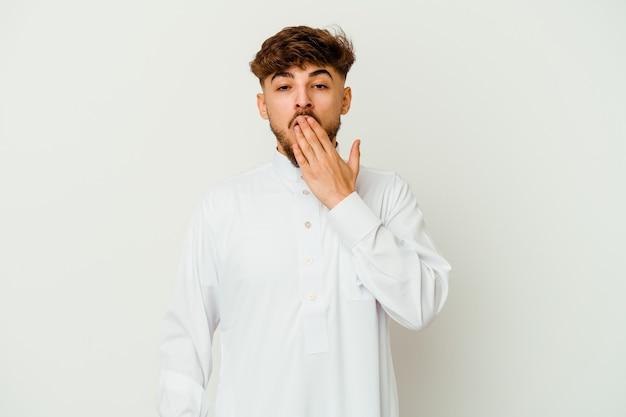手で口を覆う疲れたジェスチャーを示すあくびをしている白い壁に隔離された典型的なアラブの服を着ている若いモロッコ人男性。