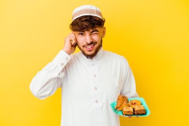 手で耳を覆うアラビアのお菓子を食べる典型的なアラビアの衣装を着た若いモロッコ人男性。