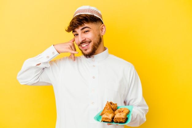 指で携帯電話の呼び出しジェスチャーを示す黄色に分離されたアラビアのお菓子を食べる典型的なアラビアの衣装を着た若いモロッコ人男性。