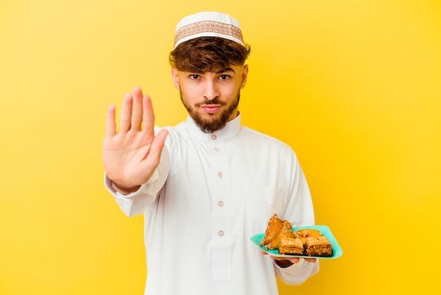 典型的なアラビアの衣装を着て食べるモロッコの若い男