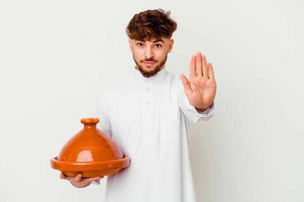 一時停止の標識を示す伸ばした手で白い立っているタジンを保持している典型的なアラビアの衣装を着ている若いモロッコ人は、あなたを防ぎます。