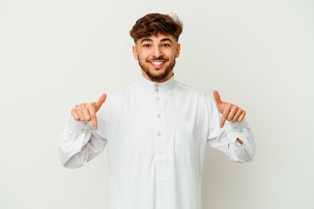 손가락, 긍정적 인 느낌으로 아래로 흰색 포인트에 고립 된 전형적인 아랍 옷을 입고 젊은 모로코 남자.