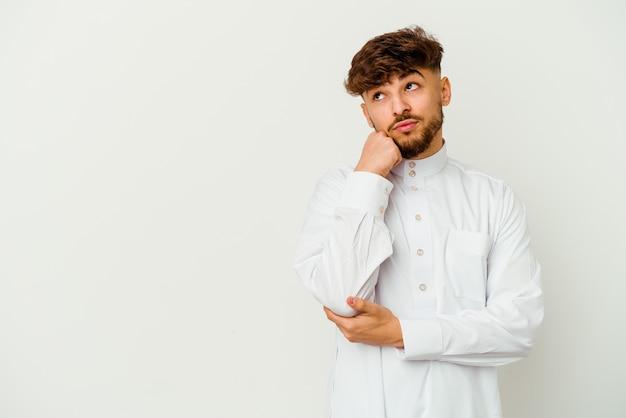 슬픈 생각에 잠겨있는 느낌, 복사 공간을 찾고 흰색 절연 전형적인 아랍 옷을 입고 젊은 모로코 남자.