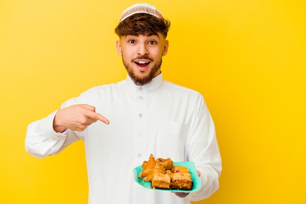 Young moroccan man wearing the typical arabic costume eating arabian sweets isolated on yellow background