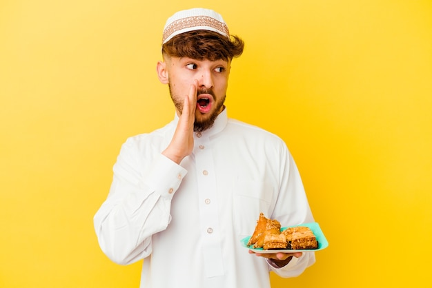 Young moroccan man wearing the typical arabic costume eating arabian sweets isolated on yellow is saying a secret hot braking news and looking aside