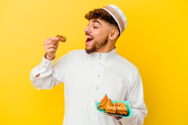 Young moroccan man wearing the typical arabic costume eating arabian sweets isolated on yellow wall