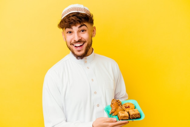 Young moroccan man wearing the typical arabic costume eating arabian sweets   laughing and having fun.