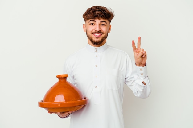 Young moroccan man wearing the typical arabic costume holding a tajine isolated on white showing number two with fingers.
