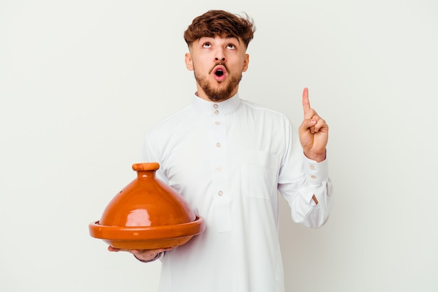Young moroccan man wearing the typical arabic costume holding a tajine   pointing upside with opened mouth.