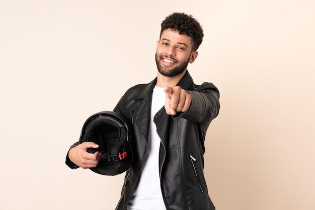 幸せな表情で正面を指すベージュの背景に分離されたオートバイのヘルメットを持つ若いモロッコ人男性