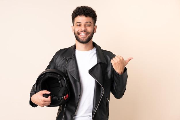 製品を提示する側を指しているベージュの背景に分離されたオートバイのヘルメットを持つ若いモロッコ人男性