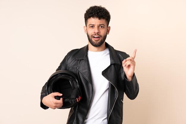 베이지 색 벽에 고립 된 오토바이 헬멧을 가진 젊은 모로코 남자는 손가락을 들어 올리면서 솔루션을 실현하려고합니다.