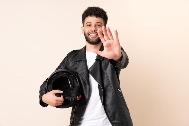 Молодой марокканский мужчина в мотоциклетном шлеме изолирован на бежевой стене, делая стоп-жест