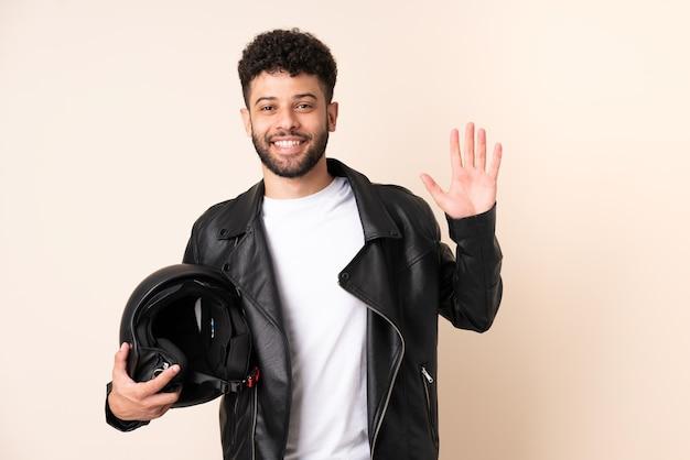 幸せな表情で手で敬礼するベージュの壁に分離されたオートバイのヘルメットを持つ若いモロッコ人男性