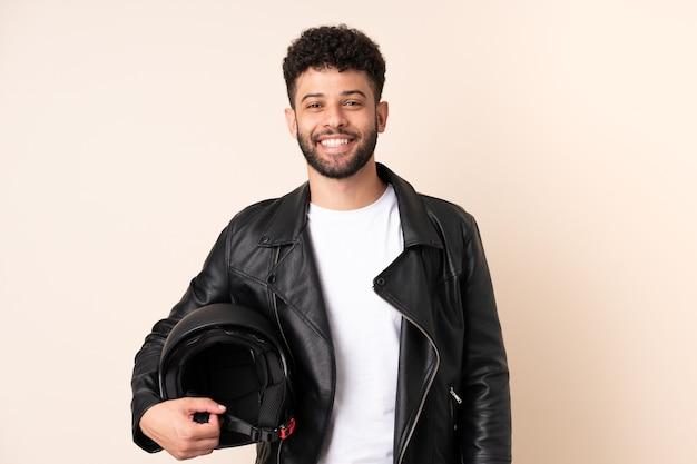 찾고있는 동안 아이디어를 생각하는 베이지 색 벽에 고립 된 오토바이 헬멧을 가진 젊은 모로코 남자