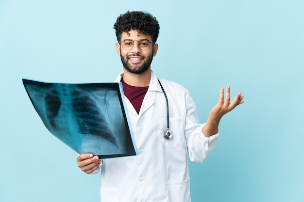 Young moroccan traumatologist in workplace isolated on blue background extending hands to the side for inviting to come