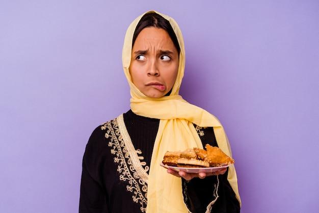 보라색 배경에 고립 된 아라비아 과자를 들고 젊은 모로코 여자 혼란, 의심스럽고 확신이 들지 않습니다.