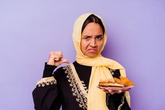 보라색 배경에 고립 된 아라비아 과자를 들고 젊은 모로코 여자는 자랑스럽고 자신감을 느낍니다.