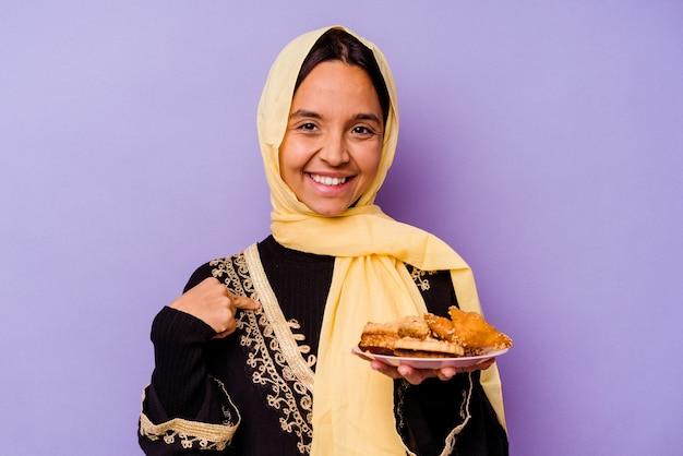 자랑스럽고 자신감, 셔츠 복사 공간을 손으로 가리키는 보라색 배경 사람에 고립 된 아라비아 과자를 들고 젊은 모로코 여자