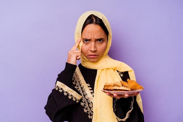 생각, 작업에 초점을 맞춘 손가락으로 사원을 가리키는 보라색 배경에 고립 된 아라비아 과자를 들고 젊은 모로코 여자.