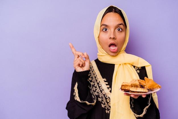 Молодая марокканская женщина, держащая арабские сладости, изолированные на фиолетовом фоне, указывая в сторону