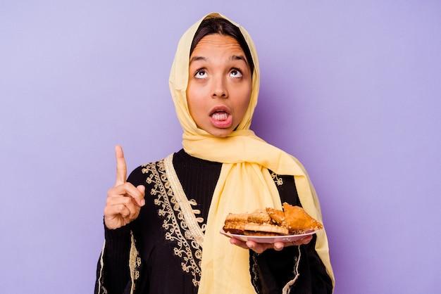 열린 된 입으로 거꾸로 가리키는 보라색 배경에 고립 된 아라비아 과자를 들고 젊은 모로코 여자.